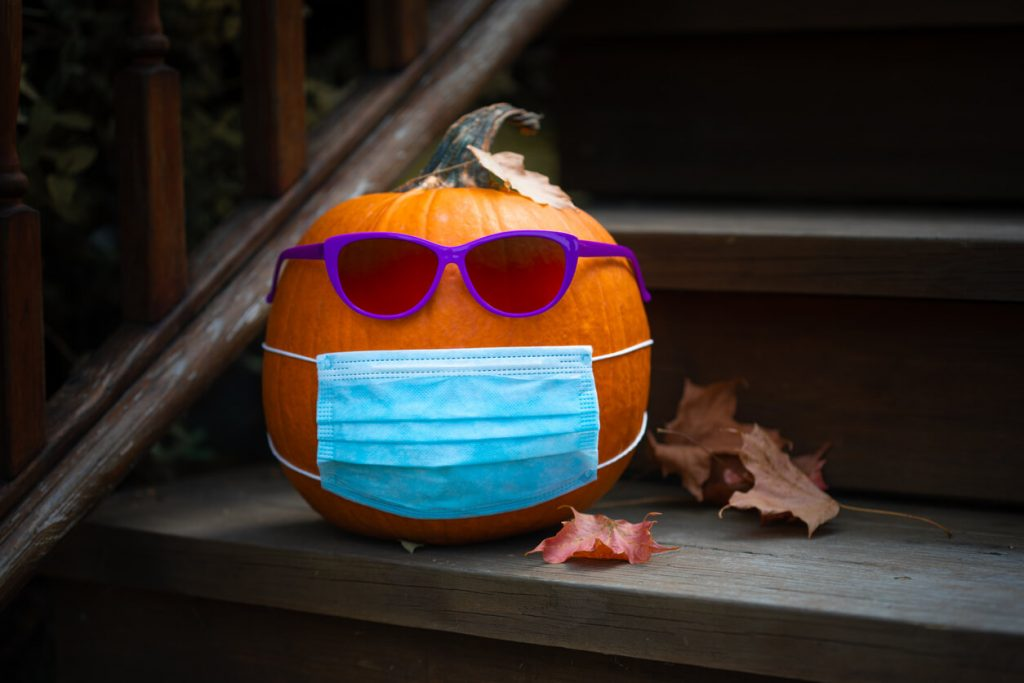 Changing times, changing seasons. Pumpkin with sunglasses and mask on steps